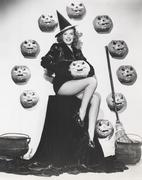 Bewitching woman sitting among carved pumpkins Stock Photos