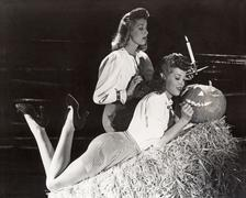Two women in a barn carving jack o'lantern Stock Photos