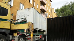 Container lifted off truck lorry at building site Stock Footage