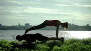 River bank. Young man and woman warming up before practice of acrobatic yoga. HD Stock Footage