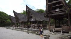 Backpacker female traveler walking around traditional batak village on Sumatra Stock Footage