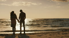 Couple in love looking at the sunset over the sea, holding hands. Cool day, the Stock Footage