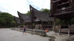 Backpacker female traveler walking around traditional batak village on Sumatra Stock Footage