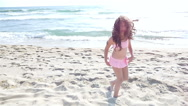 Slow motion of a cute little girl in swimsuit playing on the sea beach Stock Footage