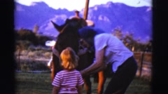 1968: mother with scarf gives horse with bridle to little girl COTTONWOOD, Stock Footage