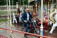 Man sitting at motorcycle on the carousel Stock Photos