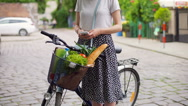 Girl standing with the bicycle on pathway and texting on smartphone Stock Footage