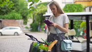 Pretty girl standing with the bicycle on the path and browsing internet on table Stock Footage