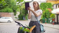 Pretty girl having a videocall on tablet while standing with bike on the path Stock Footage