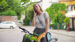 Pretty girl standing with the bike on pathway and having a headache Stock Footage