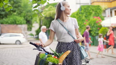 Girl listening music on headphones and standing with the bike on path Stock Footage