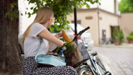 Girl sitting under the tree and looking for something in the basket Stock Footage