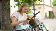 Girl sitting next to her bicycle and texting on smartphone Stock Footage