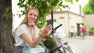 Girl sitting under the tree and doing selfies on smartphone Stock Footage