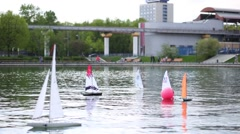 Miniature radio-controlled sailboats floats around the displacer on pond Stock Footage