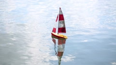 Red silver miniature radio-controlled boat on the lake surface Stock Footage