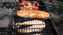 Chunks of red large fish and meat are fried on the grill at a picnic Stock Footage