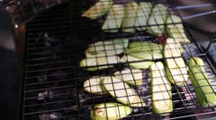 Man puts long sausage in lattice on vegetables at a picnic Stock Footage