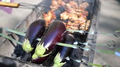 Eggplant on skewers next to the meat on the grill at sunny day Stock Footage