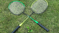 Badminton rackets on green summer grass. male and female hand takes the racket Stock Footage