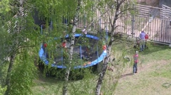 Kids jumping on a large trampoline in the trees in the yard Stock Footage