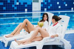 Friends dressed in bathrobes and bikini relaxing at spa next to a swimming pool Stock Photos
