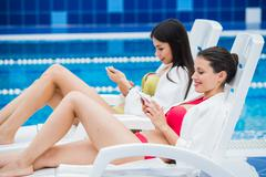 Young girls friends messaging with friend on her smartphone. Relaxation spa and Stock Photos