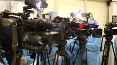 Cameramen standing at the cameras at a press conference in plant Stock Footage
