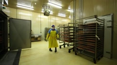 Factory worker pulls the shelving with fish out of the room in plant Stock Footage
