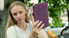 Pretty girl using tablet as a mirror and checking her appearance Stock Footage