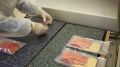 Employee arranges red fish in plastic bags on the machine for packaging Stock Footage