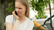 Pretty girl looking irritated while talking on cellphone, steadycam shot Stock Footage