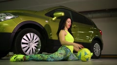 A girl sits in splits next to the car and rolls ball on floor Stock Footage