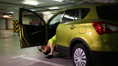 Girl doing abdominal exercises in the car on indoor parking Stock Footage