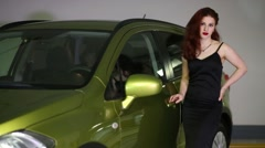 Beautiful young girl in a black dress gets into the yellow car Stock Footage