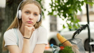 Unhappy girl sitting under the tree and listening music on headphones Stock Footage