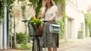 Girl walking with bicycle and chatting on cellphone, steadycam shot Stock Footage