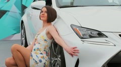Handsome model in summer dress sits near white car on exhibition Stock Footage