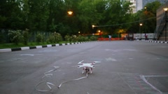 Drone with illuminated lathe flies up from asphalt at summer evening Stock Footage