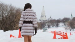 Woman in fur coat walks by test drive area with car rides at winter day Stock Footage