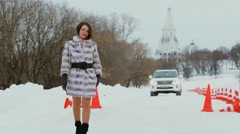 Woman in fur coat walks by snow and car rides behind at winter day Stock Footage