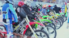 Many bikers wait on start line for start of competition at winter Stock Footage