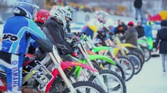 Many bikers prepares on start line before race at winter evening Stock Footage