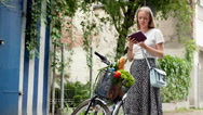 Girl standing with her bicycle and browsing internet on tablet Stock Footage