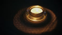 Candle flame quivers in glass candle-holder at dark Stock Footage