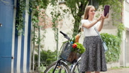Pretty girl standing with her bicycle and doing selfies on tablet Stock Footage