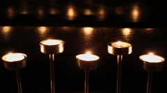 Five candles flames quiver in metal candle-holder at dark Stock Footage