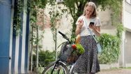 Girl standing with her bicycle and checking shopping in the basket Stock Footage
