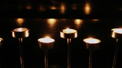 Several candles burn in metal candle-holder at dark Stock Footage