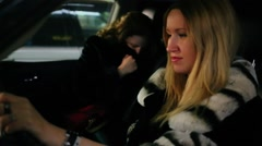 Blonde sits on driver place in car with one passenger Stock Footage